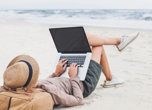 Woman on her laptop on the beach