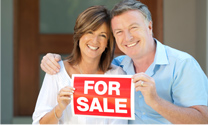 Man and woman holding up for sale sign