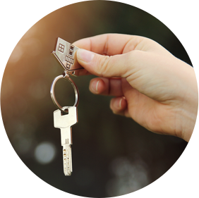 Hand holding a house keychain with a key attached